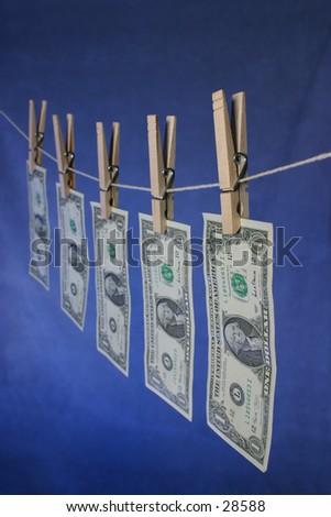 Money hanging on line. 5 US dollar bills. focus is on first dollar bill.