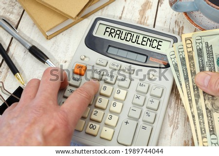 Money in hand next to a calculator and office supplies. Fraudulence - word on calculator. Stock photo ©