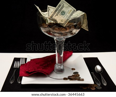 Money in large serving dish sitting  on top of dinner plate being served as though it were a dessert.