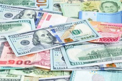 Money in multi currencies with 100 USD bill on top