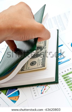 Money in notebook on business charts and diagrams