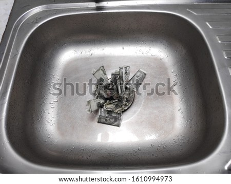 Money in Sink/ money being flushed down the sink, a metaphor for wasting cash.  To describe the financial or business that is losing or bankrupt.