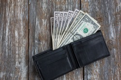 Money in the black leather wallet lying on rustic wooden background. Dollars for making purchases and byung things. Shopping time.