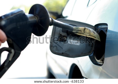 Money into the gas tank, representing the high cost of fuel