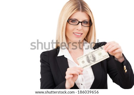 Money is a power. Confident mature businesswoman holding one hundred dollar bill and smiling while standing isolated on white