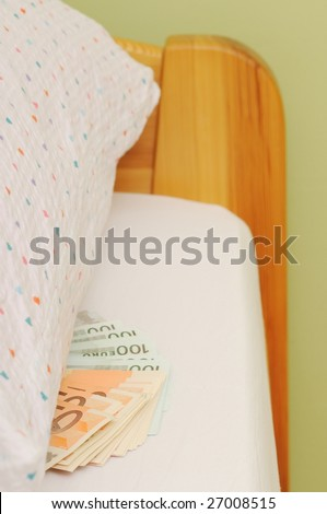 Money laid on bed under pillow