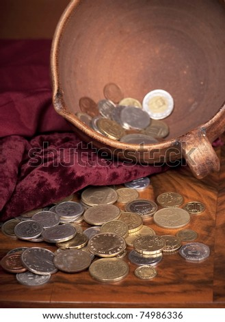 Money of different countries is combined in clay bowl