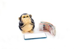 Money of different denominations monkey piggy bank and mobile phone on white background