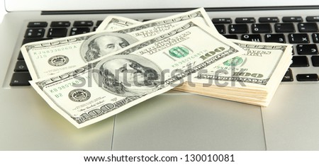 Money on laptop isolated on white
