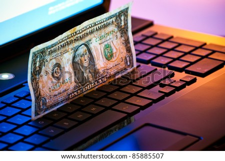 money on laptop keyboard in mixed light