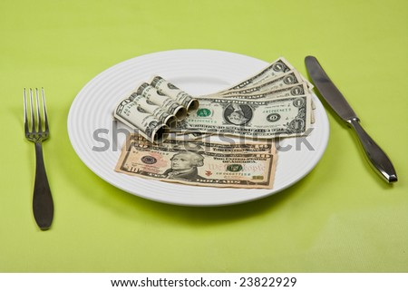 money on plate with fork and knife - stock photo