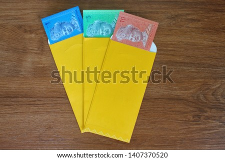 Money Packet and Malaysian Banknotes for Ramadan and Eid Fitr Celebration on wooden table. #1407370520