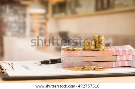 Money put on loan application form with cafe in background. concept of business loan, loan approved.