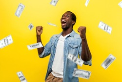 Money rain, winner and rich. happy young ecstatic motivated man standing with raised fists and shouting for joy, winner excited for success. dollars falling. indoor isolated on yellow background