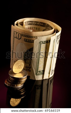 Money roll with US dollars, and euro coins isolated on white backgroun