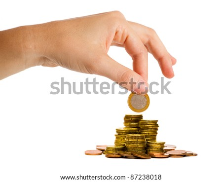 Money save concept: hand putting a coin on the top of a money pile