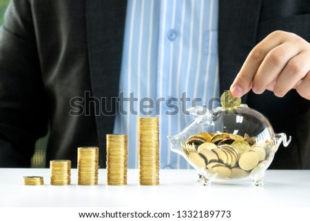 Money Saving, Business, Investment, Banking, Finance and Life Insurance concept - young businessman drop golden coin into piggy bank glass for saving money to investment in future business plan #1332189773