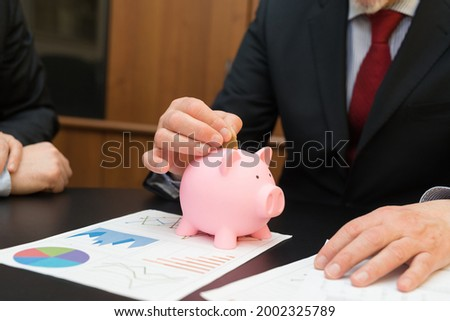 Money saving concept, businessman putting a coin in a piggy bank Photo stock ©