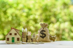 Money saving, first time asset / property buyer concept : Family couple, home model, piggy bank, dollar and tax bags, stacks of rising coins, depict budget planning for basic needs, personal expense.