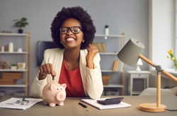 Money saving for shopping concept. Lovely satisfied, excited happy young african american woman in eyewear with yes gesture putting coin into piggybank because of income exceeds expenses significantly