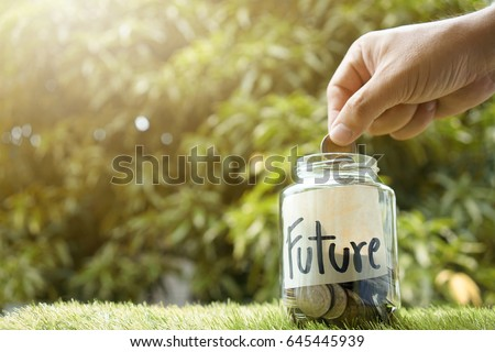 Money saving, Hand putting coin in glass jar with coins inside For now and future money. Concept of saving money for future. #645445939
