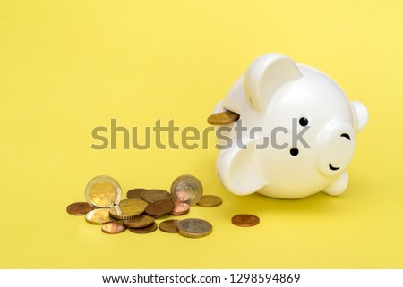 Money spilling out of the piggy bank on the yellow background #1298594869