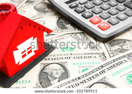 Money, the calculator and the toy house. - stock photo