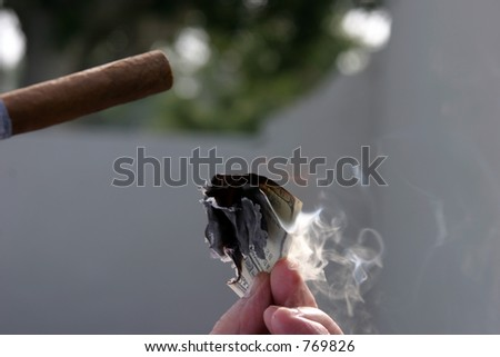 Money to burn lighting a cigar with hundreds