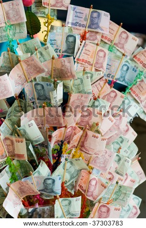 Money tree at Buddhist temple in Thailand consisting of banknotes donated by visitors for maintenance of the temple.