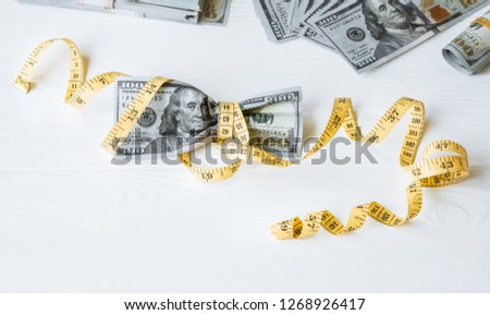 Money with a tape measure. Dollars photo. Inflation rates. Price growth. Greedy corruption concept. Bribe idea.