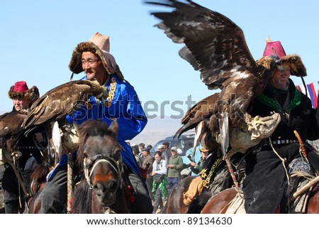 "MONGOLIA - 25 JULY: The senior Mongolians horsemen in traditional clothing with golden eagles during the festival of name ""The Golden Eagle Festival"" July 25, 2011, Mongolia - desert"
