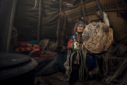 Mongolia shaman doing authentic ritual of summoning spirits. shaman with jewelry holding drum with incense. Shamanic ritual in winter. Ethnic traditions