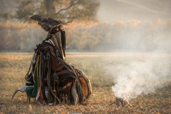 Mongolian traditional shaman performing a traditional shamanistic ritual with a drum and smoke in a forest during autumn afternoon. Ulaanbaatar, Mongolia.