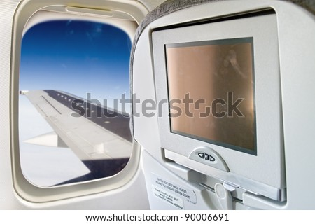 monitor and a window on the plane. Wing aircraft flying in the sky in a window plane. Blank display screen on the aircraft seat by the window.
