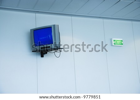Monitor mounted to wall next to exit sign in airport