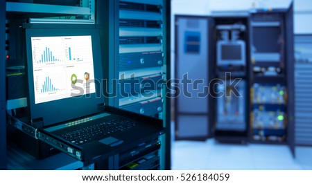Stock Photo monitor show graph information of network traffic and status of device in server room data center and blur background. blue tone
