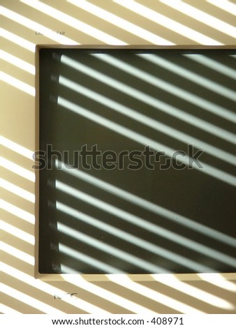 monitor swimming in shadows cast by window blinds