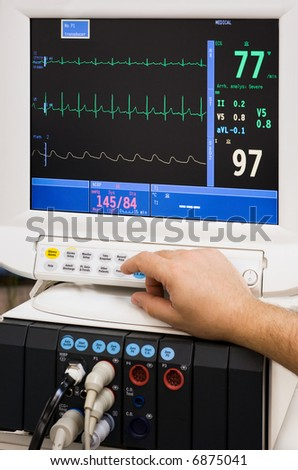 monitor with doctor's hand in intensive care unit