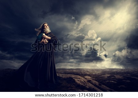 Monk Holding Bible Looking Up to God Sky Light, Old Priest in Black Robe in Storm Mountains Foto stock ©