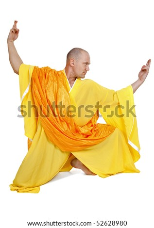Monk in orange and yellow dress exercising on white background