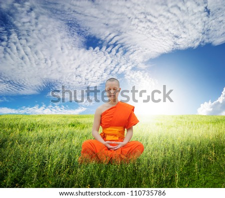 Monk meditating in grass fields and blue sky