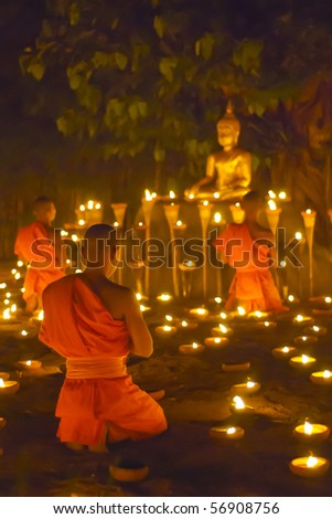 Monk pray to buddha statue and candle in Chiangmai Thailand