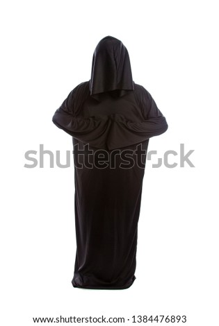 Monk wearing black robes and a hood or a person in a halloween costume of a grim reaper ghost.  The image depicts a priest in traditional or ancient clothing.  #1384476893