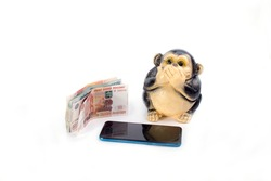 monkey piggy bank and mobile phone Different denominations money on white background