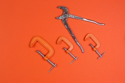 Monkey wrench and clamp, clamps on an orange background. compress, repair, construction.