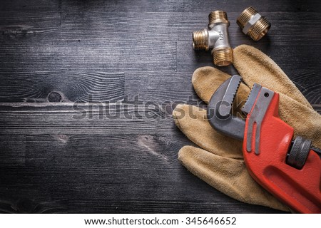 Monkey wrench brass plumbing fittings leather safety gloves construction concept.