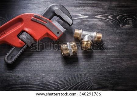 Monkey wrench brass plumbing fittings on wooden board.