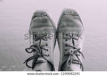 Mono chrome depth photograph of cross laced shoes. Fashion is a big part of the world and everyone has personal perspective and personal style. Shoes define a lot about an individuals.