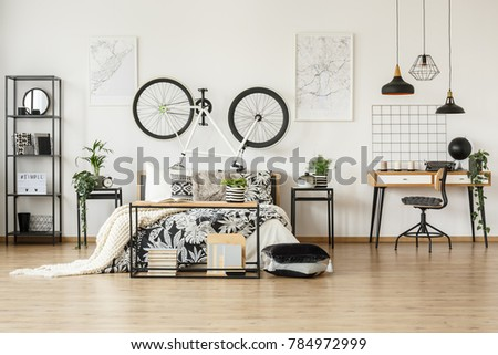 Monochromatic bedroom for a teenager with black and white bed and study space #784972999