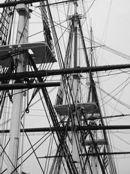 Monochromatic image of a bunch of tall masts of an old sailing-vessel.